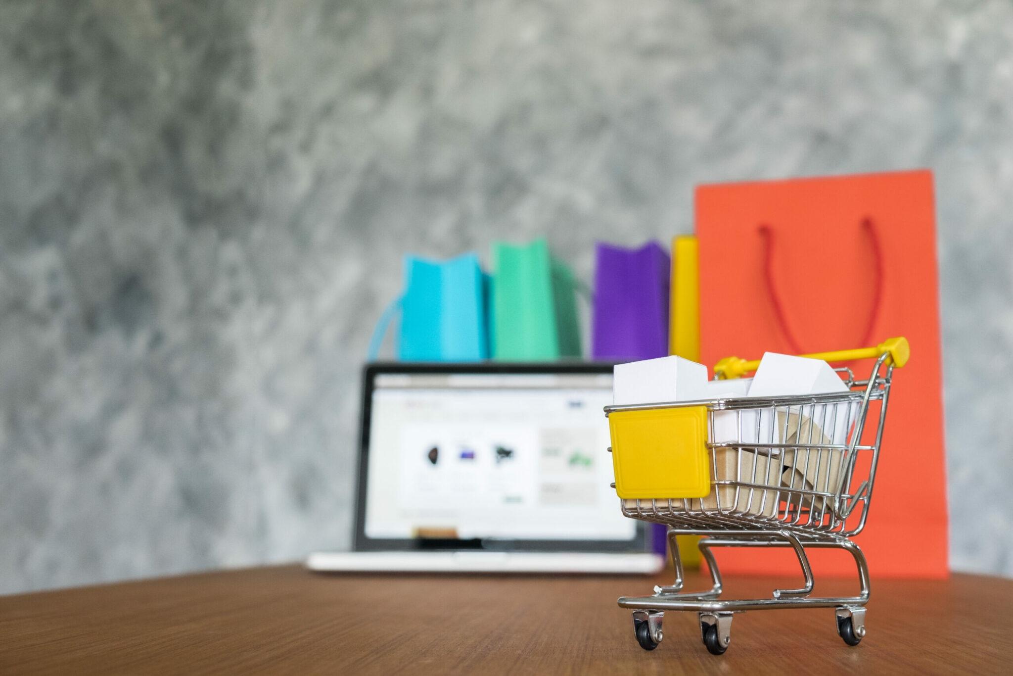 Carrinho de compras a frente do notebook representando automatização de comunicação com o cliente